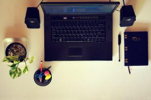 Workspace with laptop pen and notebook
